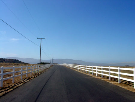 Paved road with white picket fence